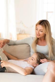 Mãe sentada ao lado da filha lendo livro