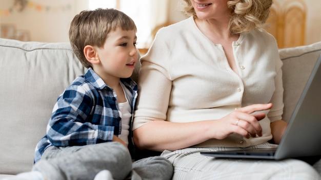 Mãe sentada ao lado de seu filho e trabalhando