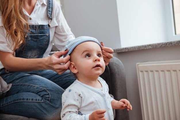 Mãe sentada e cuidando do filho pequeno em casa