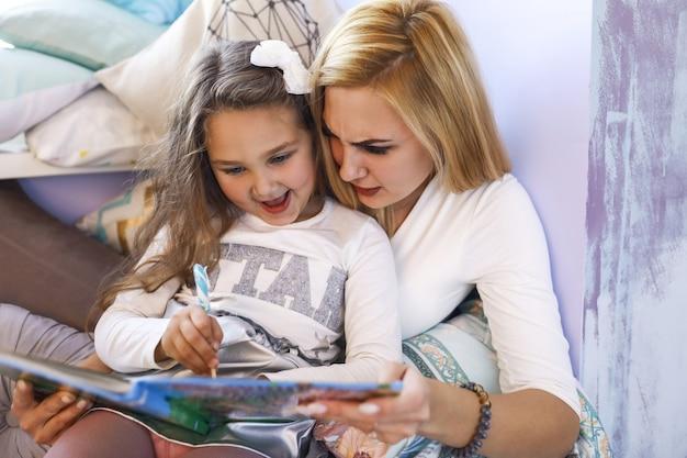 Mãe séria e filha sorriu estão escrevendo no caderno na sala iluminada