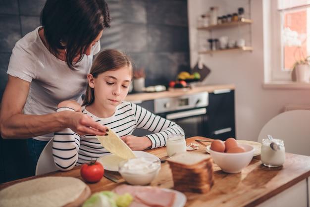 Mãe servindo café da manhã para a filha