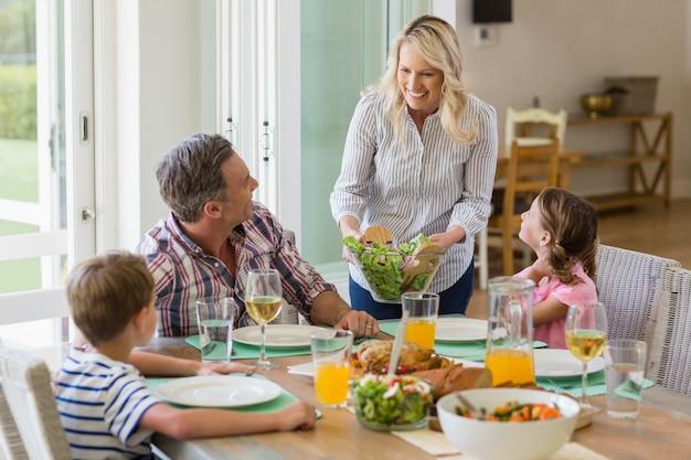 Mãe servindo comida para a família na mesa de jantar