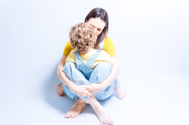 Mãe solteira adulta jovem abraçando seu filho de três anos. conceito de família monoparental. mãe solteira. amo filho