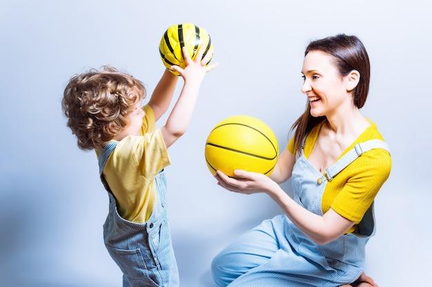 Mãe solteira adulta jovem brincando com seu filho com uma bola de basquete e futebol. conceito brincar com as crianças. mãe solteira. esportes escolares