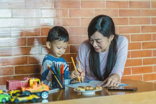Mãe solteira asiática com filho estão desenhando juntos quando vivem em casa de loft para a escola em casa
