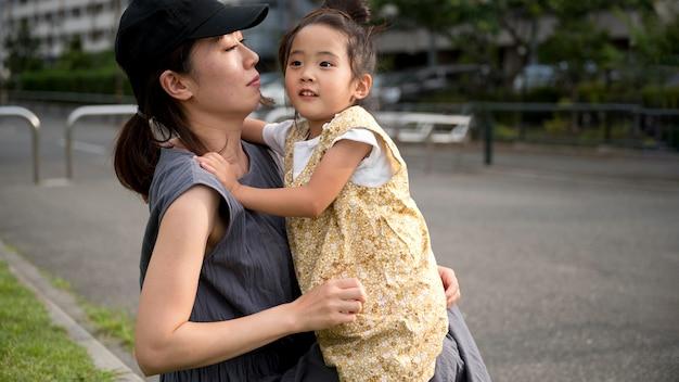 Mãe solteira brincando com a filha em um parque