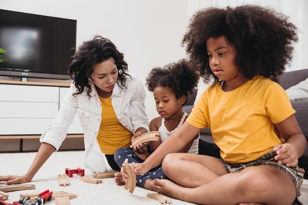Mãe solteira com duas filhas brincando de brinquedo no apartamento
