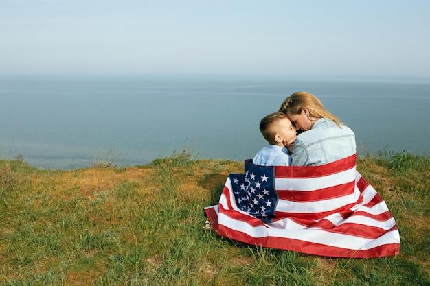 Mãe solteira com o filho no dia da independência dos eua. mulher e seu filho andar com a bandeira dos eua na costa do oceano