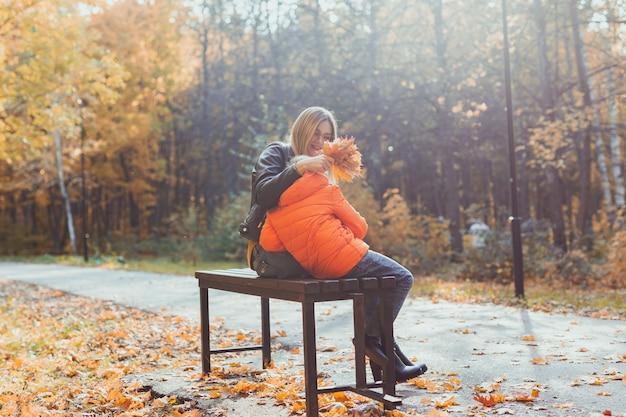 Mãe solteira e filho menino no outono no parque sentar no banco, temporada de outono e conceito de família