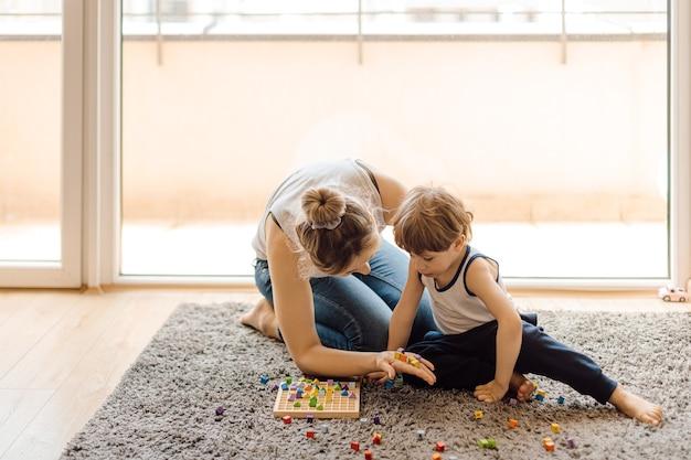 Mãe solteira ensina seu filho de 3 anos a contar. relato do ensino familiar. desenvolvimento de habilidades matemáticas. Foto Premium