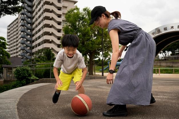 Mãe solteira jogando basquete com o filho