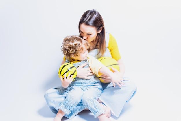 Mãe solteira, jovem adulta brincando com o filho com uma bola de basquete e futebol