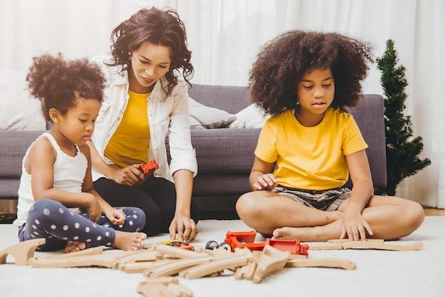 Mãe solteira que mora com duas filhas, aprendendo e brincando de quebra-cabeça em um apartamento. babá procurando ou cuidando de crianças negras na sala de estar.