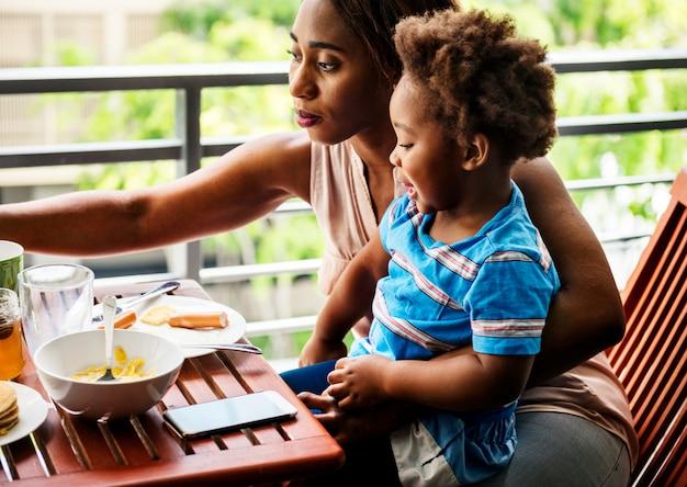 Mãe solteira tomando café da manhã com seu filho