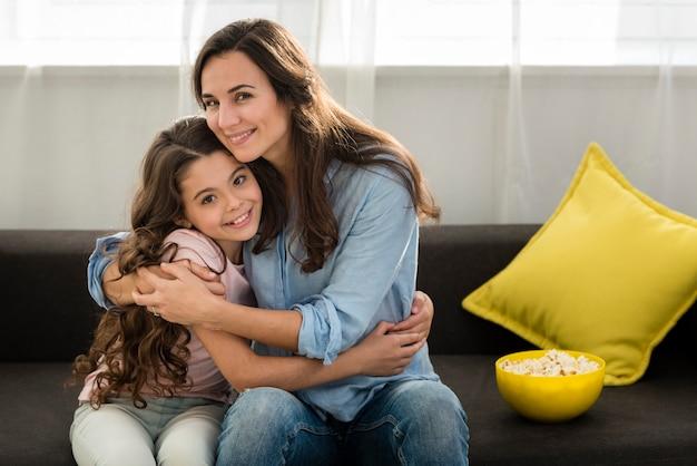 Mãe sorridente, abraçando a filha