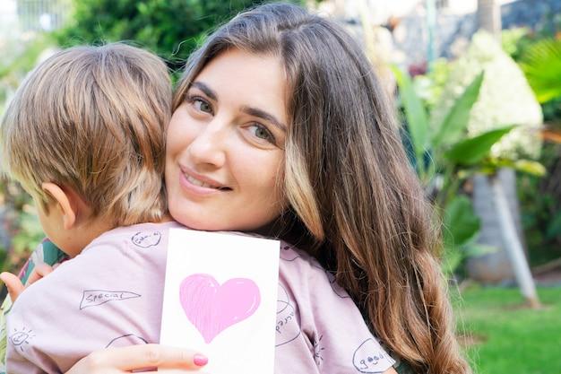 Mãe sorridente abraçando o filho no jardim de verão, dia das mães e conceito de estilo de vida familiar feliz