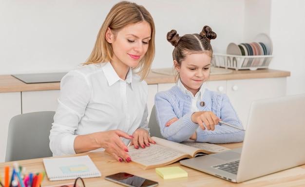Mãe sorridente, ajudando a filha em uma aula on-line
