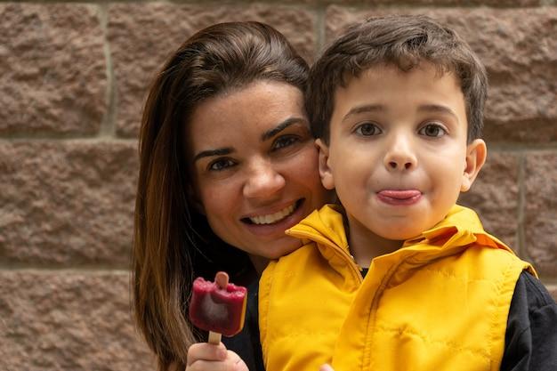 Mãe sorridente atrás do filho segurando um picolé