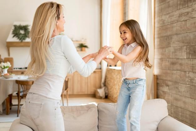 Mãe sorridente brincando com a filha em casa