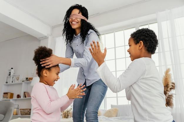 Mãe sorridente brincando com os filhos em casa com os olhos vendados