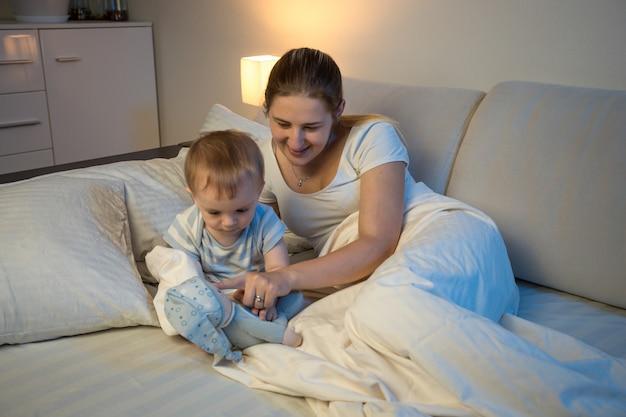Mãe sorridente brincando com seu bebê deitado na cama à noite e brincando com brinquedos