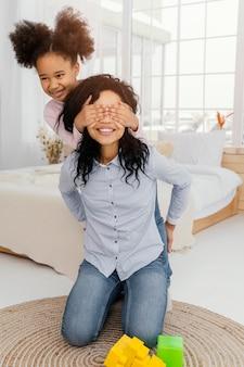 Mãe sorridente brincando em casa com a filha