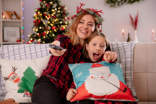 Mãe sorridente com coroa de azevinho segura o controle remoto da tv e aponta, sentada no sofá, curtindo o natal com a filha em casa