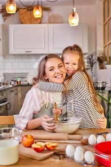 Mãe sorridente com filha abraçando enquanto cozinha, preparando a massa para assar biscoitos.