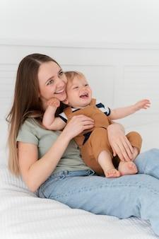 Mãe sorridente com foto média segurando a criança