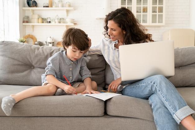 Mãe sorridente da escola em casa ajuda o filho pequeno a escrever no caderno durante o resto do trabalho remoto no laptop