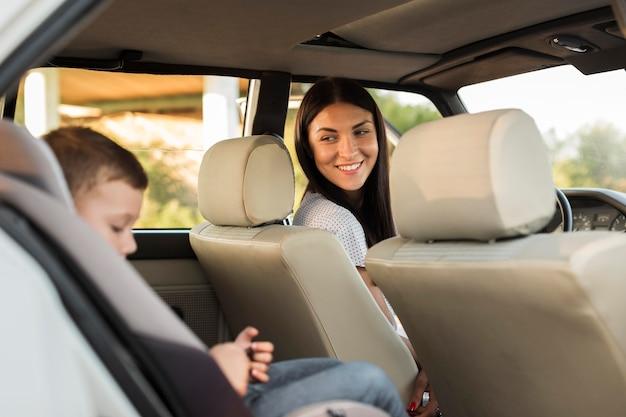 Mãe sorridente de tiro médio observando criança