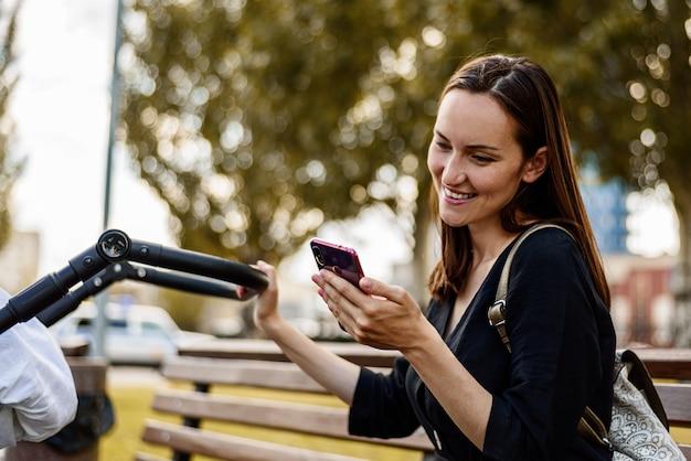 Mãe sorridente de vestido preto, mulher sentada com smartphone nas mãos
