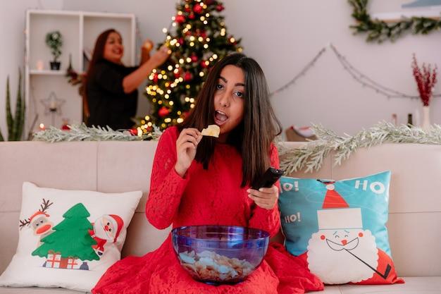 Mãe sorridente decora a árvore de natal e olha para a filha comendo uma tigela de batata frita sentada no sofá, aproveitando o natal em casa