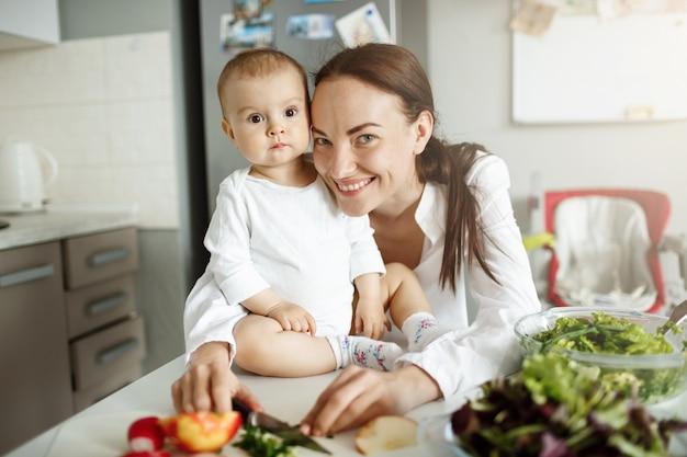 Mãe sorridente e feliz com seu bebê posando na cozinha