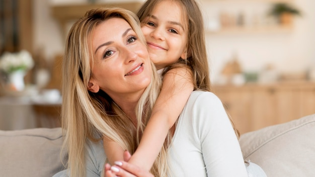 Mãe sorridente e filha abraçadas em casa
