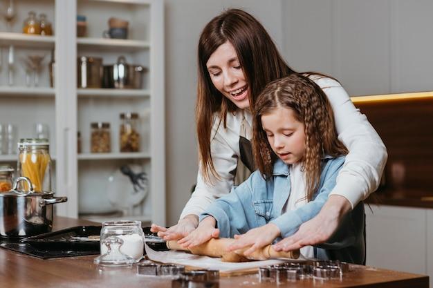 Mãe sorridente e filha cozinhando juntas em casa