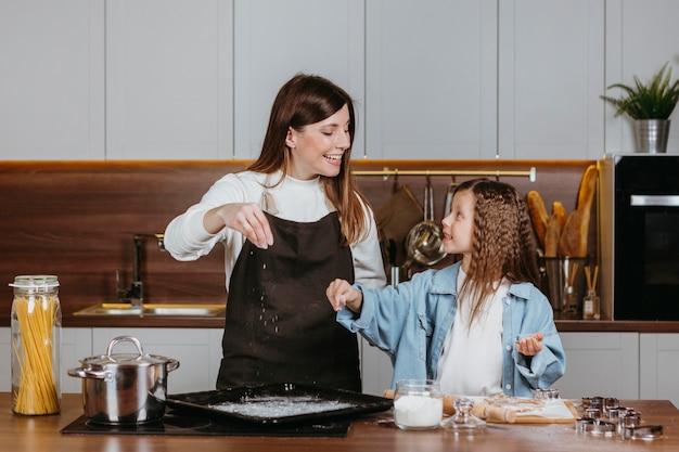 Mãe sorridente e filha cozinhando juntas na cozinha de casa
