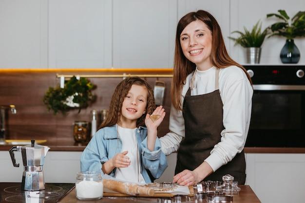 Mãe sorridente e filha cozinhando juntas na cozinha