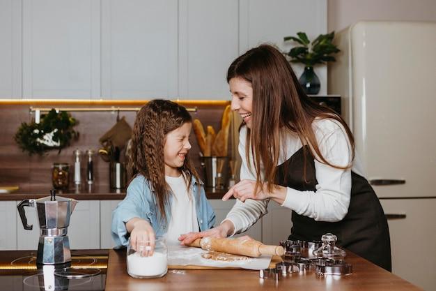 Mãe sorridente e filha cozinhando na cozinha de casa