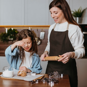 Mãe sorridente e filha cozinhando na cozinha