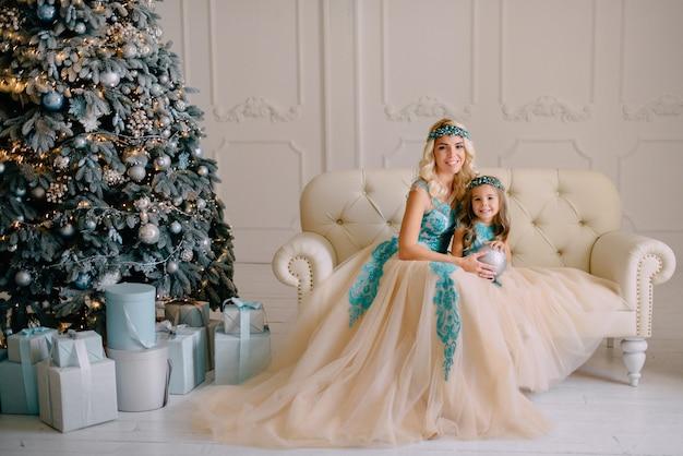 Mãe sorridente e filha em vestidos luxuosos estão sentadas no sofá