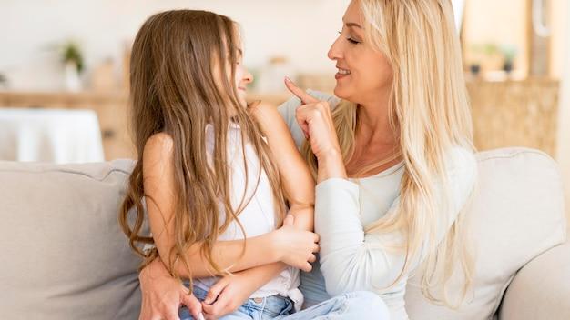 Mãe sorridente e filha passando um tempo juntas em casa