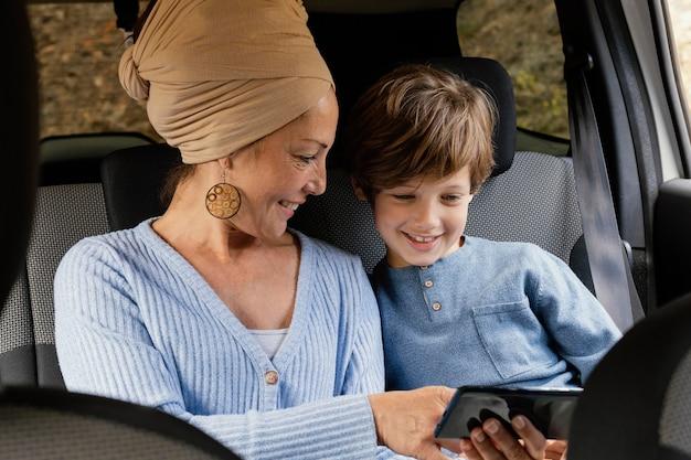 Mãe sorridente e filho no carro usando celular