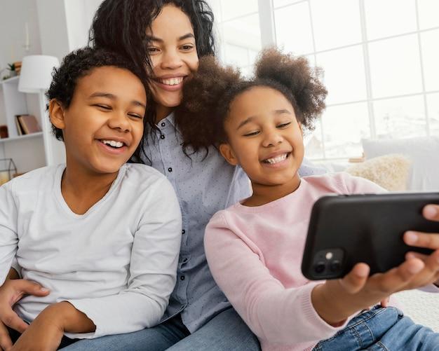 Mãe sorridente e filhos tirando selfie em casa