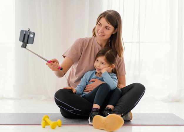 Mãe sorridente e menina tirando uma selfie completa