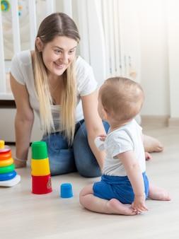 Mãe sorridente montando pirâmide de brinquedo com seu filho