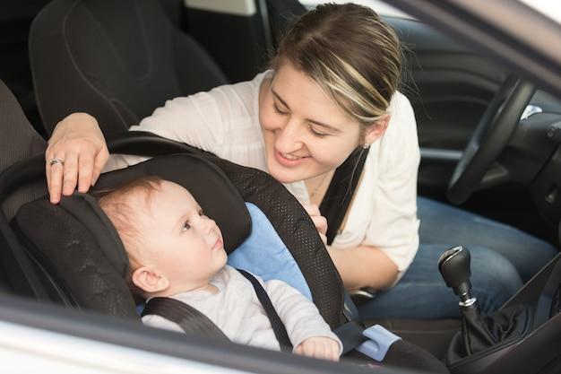 Mãe sorridente no carro com seu filho na cadeira de segurança