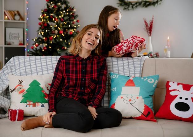 Mãe sorridente olha para o lado sentada no sofá e a filha animada segurando um pacote de presente e curtindo o natal em casa