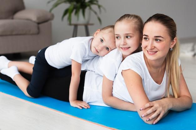 Mãe sorridente posando com filhas felizes em casa no tapete de ioga