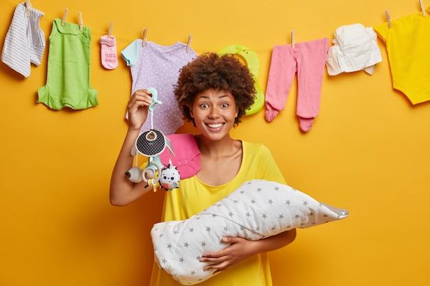 Mãe sorridente positiva segura brinquedo móvel para bebê, posa com o filho recém-nascido nas mãos, sendo mãe feliz e gosta da maternidade, expressa boas emoções, posa em casa, corda com roupas secando atrás